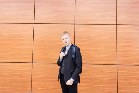 the serious schoolboy in a suit on the street