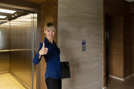 the Beautiful business blonde comes out of elevator in office 免版税图像