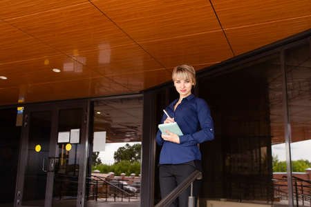 the blonde with a notebook on the street