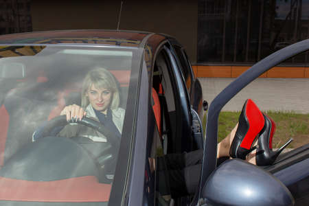 the Happy blonde having fun in the car 免版税图像
