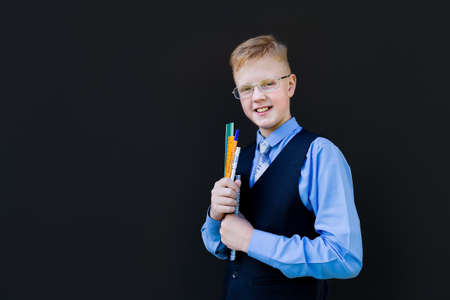 the schoolboy in glasses against the black wall