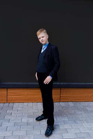 the Boy in school uniform against black wall, back to school