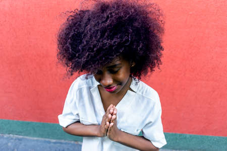 An African American woman makes a gesture of gratitude