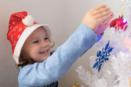 the Happy little girl dresses up Christmas tree 스톡 콘텐츠