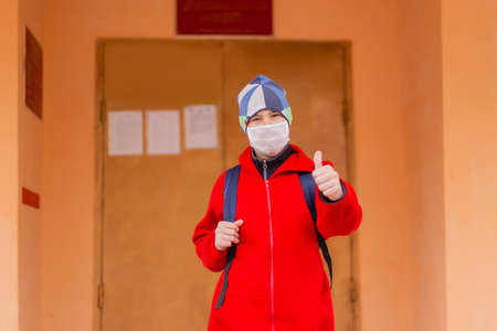 the Schoolboy shows class in protective mask 写真素材
