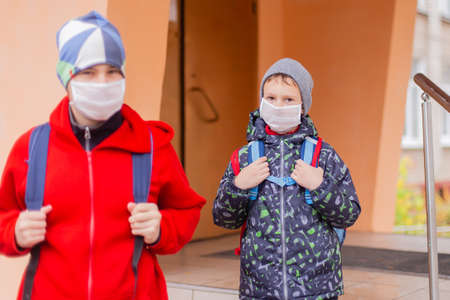 schoolboy walks out of school wearing protective mask