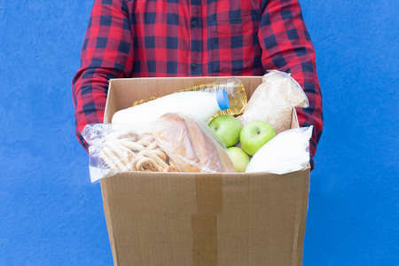 the volunteer with a box of food on a blue background, donations