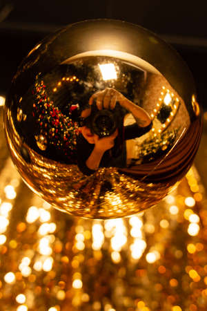 the Gold blurred background with glitter photographer in reflection, 2021 trend