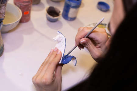 girl paints a clay product in the workshop