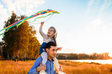 happy father with a little daughter, having fun in nature, in the rays of the sunset.