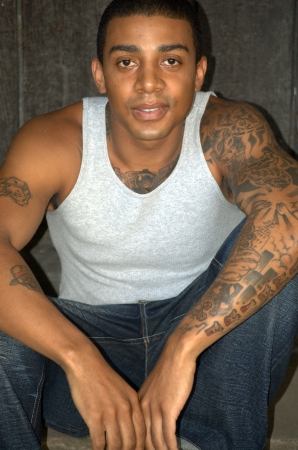 an inmate: Black man with tattoos sitting Stock Photo