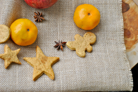 Christmas gingerbread man and a star anise and tangerines on a napkin from a rough fabric photo