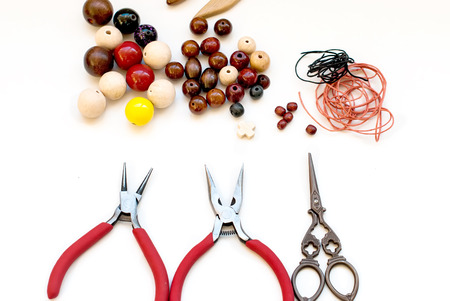 colorful wooden beads, scissors, and tools for creating fashion jewelry in the manufacturing process on a white table photo