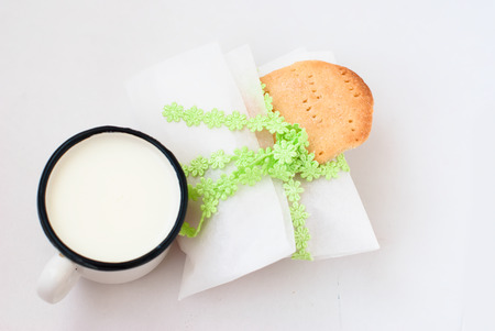 envelope with homemade cookies from parchment, cookies and a mug of milk on a white background, high key photo