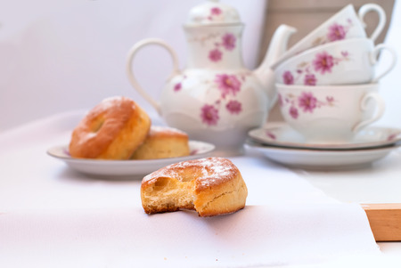 tea service: Full-flavored homemade buns from yeast dough with powdered sugar on a plate and tea service