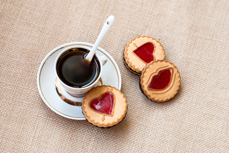 kiss biscuits: cup of coffee and a cookie with a heart of marmalade. Valentines Day card Stock Photo