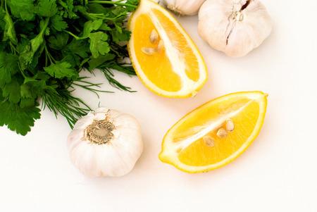 ajo: Los aromas para cocinar la carne. rodajas de lim�n, los dientes de ajo y el perejil en el fondo blanco Foto de archivo