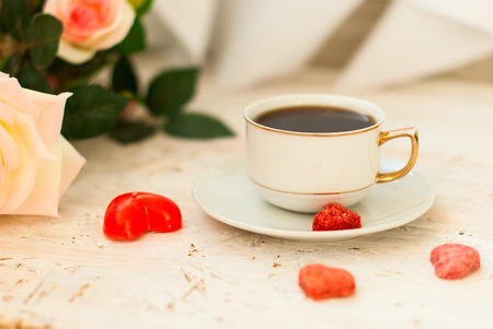 kiss biscuits: cup of coffee, sugar hearts and a bouquet of cream roses on a white background, greeting card for Valentines Day