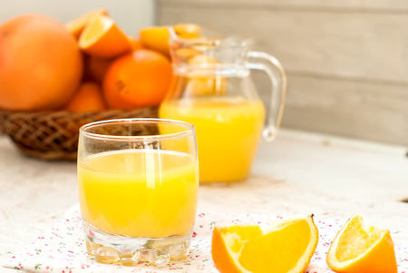 orange juice in a glass and slices of orange on the background basket with oranges and juice carafe photo