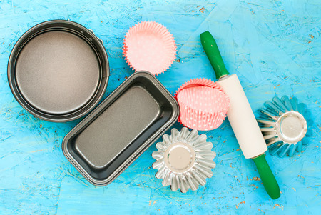 bakeware: cake pans and round metal bakeware, wooden rolling pin on a wooden background