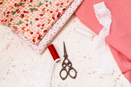 set of colorful fabrics, spools of thread and scissors. accessories for cutting and sewing photo