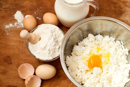 queso blanco: harina, queso cottage en un tazón y la leche en una jarra. Huevos. productos para la fabricación de queso sobre una tabla de cortar de madera
