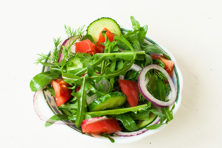 dill and parsley: Spring salad with fresh lettuce rukolla, tomato, cucumber, radish, onion kolechekkrasnogo, dill, parsley, seasoned with sunflower oil in a bowl on a white background
