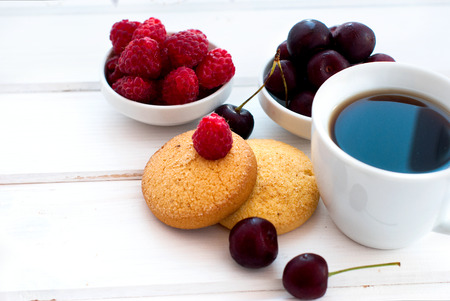light breakfast: cup of black strong coffee and two biscuits with berries - raspberries and cherries, summer light breakfast