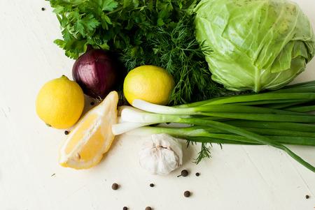 ajo: conjunto de verduras frescas para la ensalada - joven repollo, cebolla verde, cebolla roja, eneldo y perejil, lim�n y ajo en un fondo de madera blanca