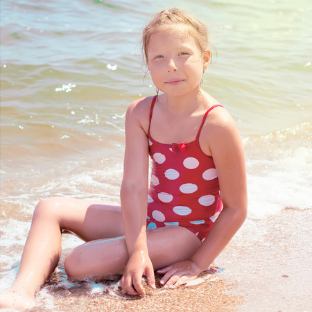 children swimsuit: Happy little child, adorable blonde toddler girl wearing colorful swimsuit playing on the beach Azov Sea making ice cream from sand using plastic toys