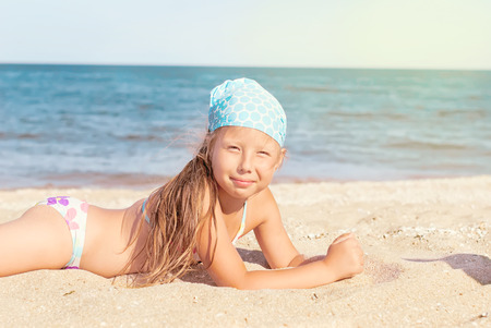 Happy little child, adorable blonde toddler girl wearing colorful swimsuit playing on the beach Azov Sea making ice cream from sand using plastic toys