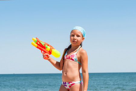 girl plays with a water pistol at the beach on the shores of the Sea of Azov