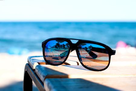 gafas de sol: gafas de espejo sobre la mesa en la playa con vistas al mar Foto de archivo