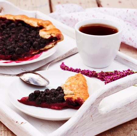 black currants: black currants biscuit on a plate, a cup of black coffee and fruit for breakfast