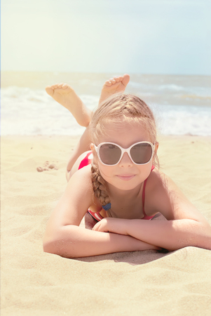 little  child: Happy little child, adorable blonde toddler girl wearing colorful swimsuit playing on the beach Azov Sea making ice cream from sand using plastic toys
