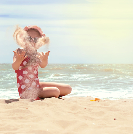 little girl swimsuit: Happy little child, adorable blonde toddler girl wearing colorful swimsuit playing on the beach Azov Sea making ice cream from sand using plastic toys, selective focus, toned photo Stock Photo