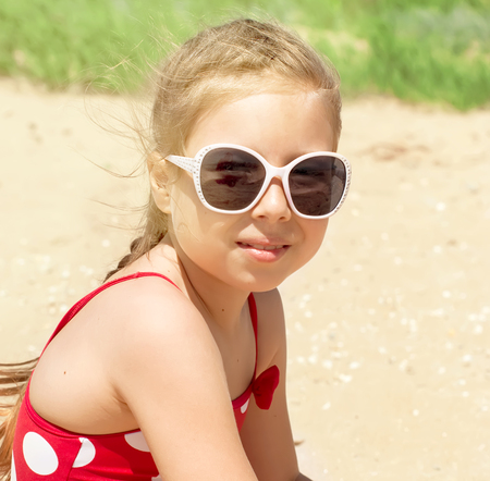 little blonde girl: Happy little child, adorable blonde toddler girl wearing colorful swimsuit playing on the beach Azov Sea making ice cream from sand using plastic toys