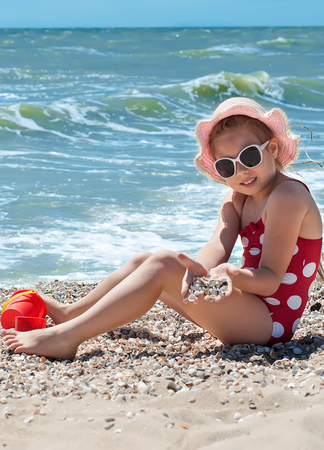 azov: Happy little child, adorable blonde toddler girl wearing colorful swimsuit playing on the beach Azov Sea making ice cream from sand using plastic toys