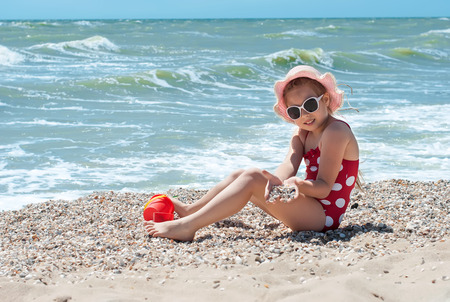 little girl swimsuit: Happy little child, adorable blonde toddler girl wearing colorful swimsuit playing on the beach Azov Sea making ice cream from sand using plastic toys