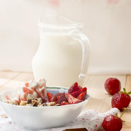 the milk jug: oatmeal with strawberries, yogurt and strawberry topping, milk jug and strawberries for breakfast  toned image, selective focus