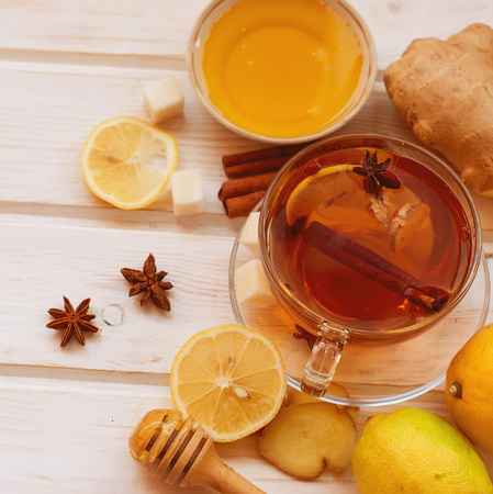 Cup of Ginger tea with lemon and honey on dark blue background, top view 免版税图像