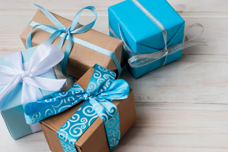 Four gift boxes in wrapping paper with ribbons lying on a white wooden background, selective focus, toned photo 免版税图像
