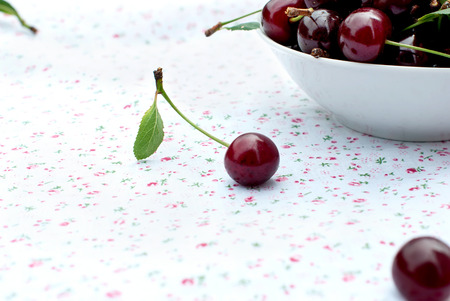 summer fruit: cherry on the table next to the plate of cherries