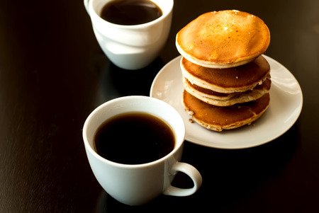 dairying: cup of black coffee and strong Pancake breakfast on black table