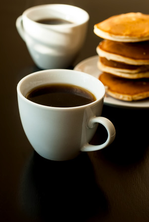vacas lecheras: cell phone and a cup of black coffee and strong Pancake breakfast on black table
