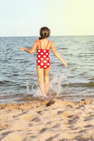 azov sea: little girl quickly comes to the Azov Sea at sunset