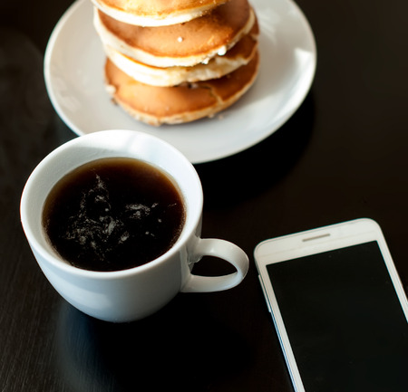 cell phone and a cup of black coffee and strong Pancake breakfast on black table