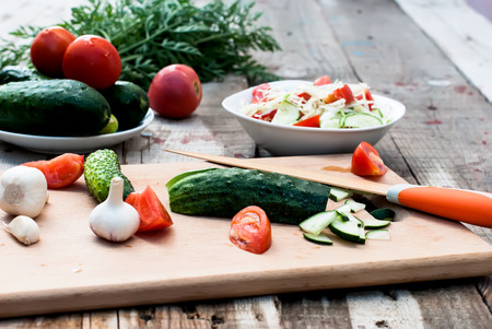 english cucumber: Cucumber and tomato slices on a cutting board Stock Photo