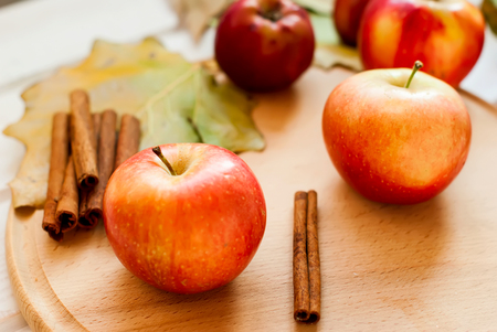 fallen fruit: Ripe red apples autumn harvest on a wooden background  and fallen leaves of the trees