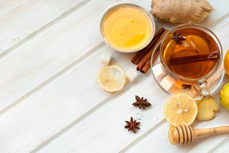 Taza de té de jengibre con limón y miel sobre fondo azul oscuro, vista desde arriba